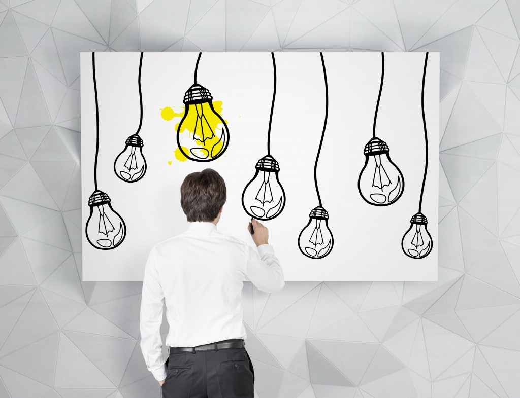 standing-businessman-draws-lightbulbs-gets-big-ideas